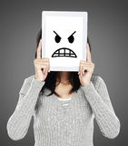 Woman showing angry emotion icon. Woman cover her face with tablet showing angry emotion icon Royalty Free Stock Photography