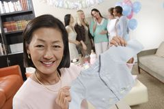 Woman Showing Baby Clothes At A Baby Shower Stock Images