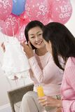 Woman Showing Baby Shower Clothes To Friend Stock Photo