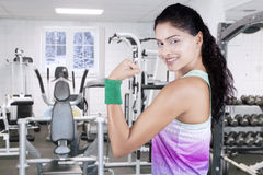 Woman showing bicep at gym in winter season Royalty Free Stock Photo