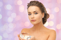 Woman showing big diamond over pink lights Royalty Free Stock Photos