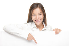 Woman showing billboard sign. Woman showing and pointing at blank billboard sign banner, Young smiling Chinese Asian / Caucasian female model. Isolated on white stock images