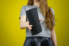 Woman showing blank black flyer paper. Leaflet presentation. Pam Stock Photography