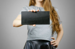 Woman showing blank black flyer paper. Leaflet presentation. Pam Stock Photo