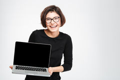 Woman showing blank laptop computer screen. Laughing woman showing blank laptop computer screen isolated on a white background Royalty Free Stock Photo