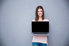 Woman showing blank laptop computer screen. Smiling woman showing blank laptop computer screen Stock Photography