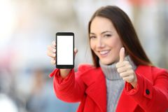 Woman showing smart phone screen in winter Stock Images
