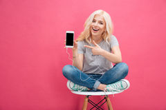 Woman showing blank smartphone screen. Cheerful woman sitting on the chair and showing blank smartphone screen over pink background Royalty Free Stock Photography