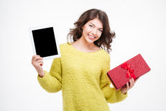 Woman showing blank tablet computer screen and holding gift box Royalty Free Stock Images