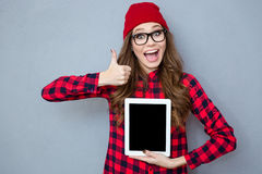 Woman showing blank tablet computer screen and thumb up Stock Photography