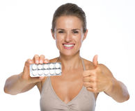 Woman showing blistering package of pills and thumbs up Stock Image