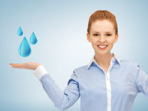Woman showing blue water drops Royalty Free Stock Photography