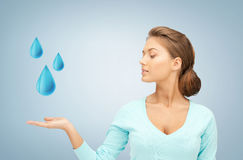 Woman showing blue water drops Royalty Free Stock Photos