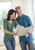 Woman Showing Blueprint To Husband In New House. Happy mature women showing plan on blueprint to husband in new house Stock Photography