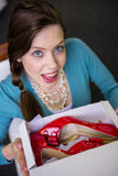 Woman showing box with red shoes Stock Photography