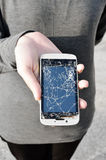 Woman showing broken smartphone. With crashed screen stock image