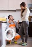 Woman showing broken washing machine Royalty Free Stock Images