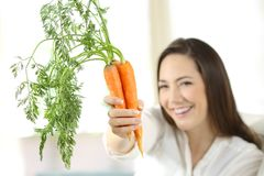 Woman showing a bundle of carrots. Happy woman showing a bundle of carrots sitting on a couch in the living room at home Stock Image