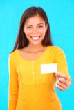 Woman showing business card. Exotic young woman on colorful background holding a blank business card with copy space Royalty Free Stock Photography