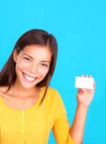 Woman showing business card / sign. Beautiful young ethnic woman presenting a blank business card, on a bright blue background Royalty Free Stock Images