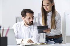 Woman showing calculator to boss Stock Photo