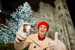 Woman showing camera and thumbs up in Christmas Florence, Italy. Young woman showing digital camera and thumbs up while in front of Christmas tree near Duomo in stock photo
