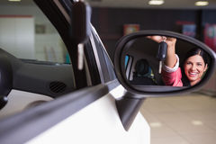 Woman showing car key in rear view mirror Stock Image