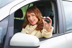 Woman showing car keys. Beautiful woman sitting in a car and showing keys out the window Stock Photos