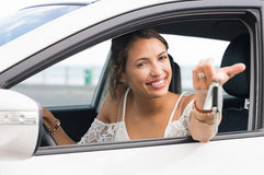 Woman showing car keys. Multiethnic woman showing new car keys and car. Young smiling girl driving her new car and looking at camera. Portrait a young happy Stock Photos