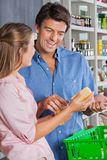 Woman Showing Cheese To Man In Supermarket Royalty Free Stock Photography