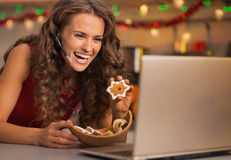 Woman showing christmas cookies while having video chat on laptop. Smiling young woman showing christmas cookies while having video chat on laptop stock image