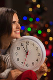 Woman showing clock in front of Christmas lights Stock Image