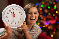 Woman showing clock in front of Christmas tree Royalty Free Stock Photo