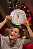 Woman showing clock in front of Christmas tree Royalty Free Stock Images