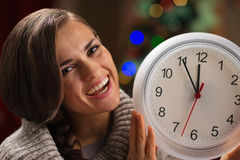 Woman showing clock in front of Christmas tree Royalty Free Stock Photos