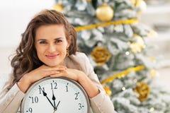 Woman showing clock near christmas tree Royalty Free Stock Image