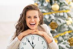 Woman showing clock near christmas tree Stock Photography