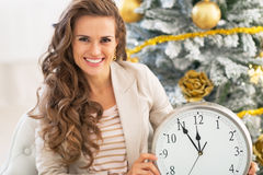 Woman showing clock near christmas tree Stock Photography