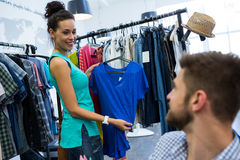Woman showing clothes to man. Woman showing clothes to men at clothes store Royalty Free Stock Photos