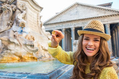 Woman showing coin near fountain of the pantheon Stock Photo