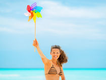 Woman showing colorful windmill toy on beach Stock Images