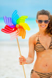 Woman showing colorful windmill toy on beach Stock Image