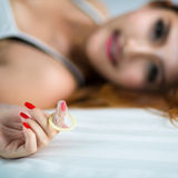 Woman showing a condom on bed Royalty Free Stock Images