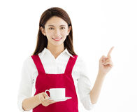 Woman showing cup of coffee and  pointing gesture Royalty Free Stock Images