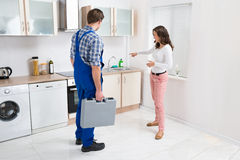 Woman Showing Damage In Sink To Plumber Stock Photos