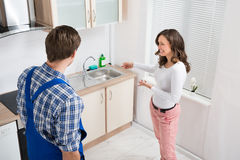 Woman Showing Damage In Sink To Plumber Stock Image