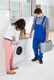 Woman Showing Damage In Washing Machine To Repairman Stock Photo