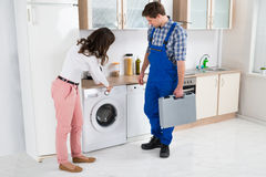 Woman Showing Damage In Washing Machine To Repairman Stock Photos