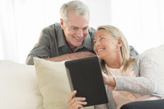Woman Showing Digital Tablet To Man At Home Royalty Free Stock Photography
