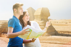 Woman Showing Direction To Man Holding Map. In Front Of Pyramid Of Egypt Royalty Free Stock Photos